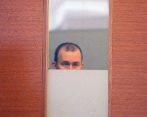Officer Keith Wilbur peers through the glass in a door as he hid from view during his arraignment at Taunton Trial Court. (Photo: Mike Gay/Taunton Gazette)